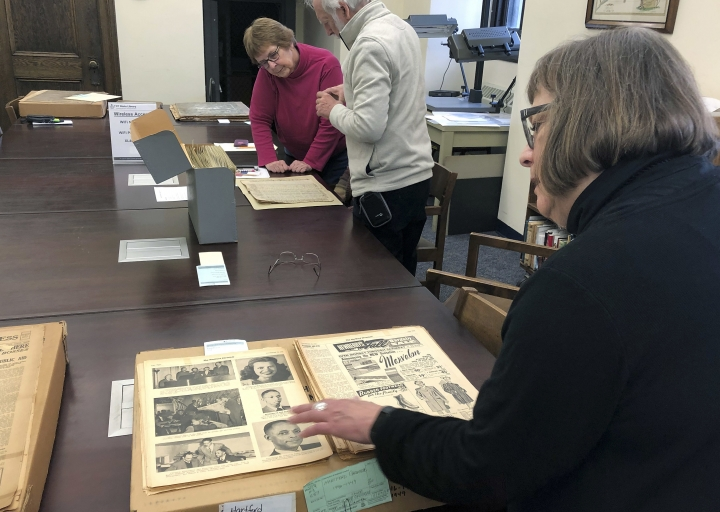 In this Nov. 29, 2018 photo, Christine Gauvreau, project coordinator for the Connecticut Digital Newspaper Project, pages through old issues of the Hartford Chronicle, a World War II era black-owned and operated newspaper, at the Connecticut State Library in Hartford, Conn. Microfilm from this and other incarnations of the newspaper is being digitized as part of the United States Newspaper Program. (AP Photo/Susan Haigh)