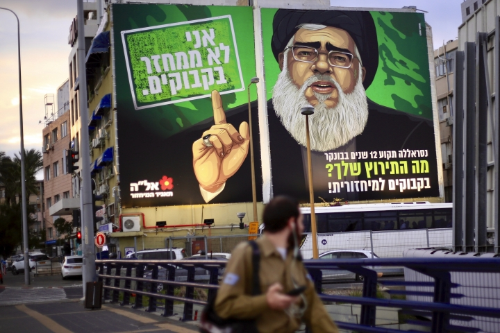 """A billboard shows Hezbollah militant leader Hassan Nasrallah above a major highway in Tel Aviv, Israel, Sunday, Feb. 10, 2019, as the face of an eye-catching, satirical recycling campaign. Above Nasrallah's finger reads the caption: """"I don't recycle bottles."""" and beneath him, the poster says: """"Nasrallah has been stuck in a bunker for 12 years. What is your excuse?"""". (AP Photo/Ariel Schalit)"""
