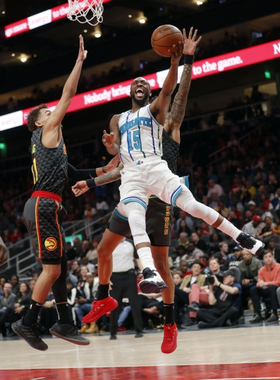 Charlotte Hornets guard Kemba Walker (15) scores as Atlanta Hawks guard Trae Young (11) defends during the second half of an NBA basketball Saturday, Feb. 9, 2019, in Atlanta. Charlotte won 129-120. (AP Photo/John Bazemore)
