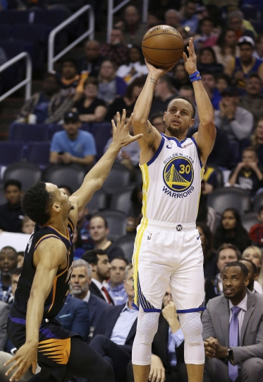 Golden State Warriors guard Stephen Curry (30) shoots over Phoenix Suns guard Elie Okobo during the first half of an NBA basketball game Friday, Feb. 8, 2019, in Phoenix. (AP Photo/Ross D. Franklin)