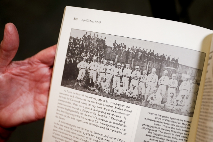 """Greg Rhodes, the Cincinnati Reds baseball team historian, holds a copy of The First Boys of Summer to a page showing a photograph of the Cincinnati Red Stockings in 1870 during an interview at the Cincinnati Reds Hall of Fame, Tuesday, Jan. 8, 2019, in Cincinnati. The Reds will play games in 15 sets of throwback uniforms, including navy blue and a """"Palm Beach"""" style, during a season-long celebration of the 1869 Red Stockings who pioneered professional baseball. (AP Photo/John Minchillo)"""