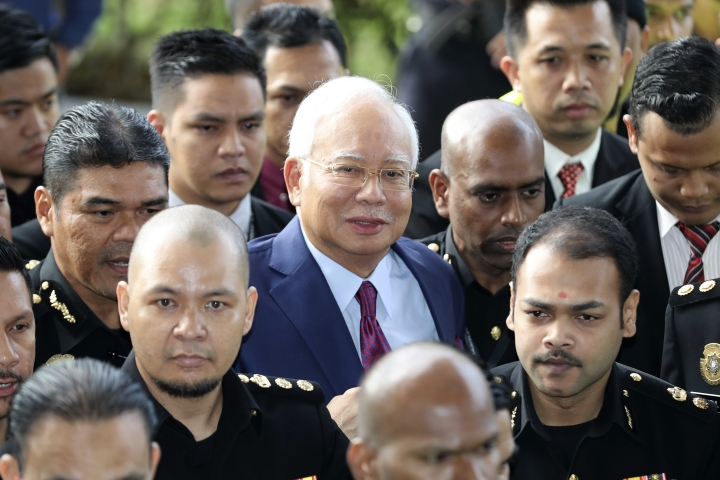 FILE - In this July 4, 2018, file photo, former Malaysian Prime Minister Najib Razak, center, arrives at a court house in Kuala Lumpur, Malaysia. Najib is hardly lying low ahead of his corruption trial set to begin Tuesday, Feb. 12, 2019, on charges related to the multibillion-dollar looting of the 1MDB state investment fund. He's crooned about slander in an R&B video and vilified the current government on social media to counter portrayals of him as corrupt and out of touch. Najib denies wrongdoing and his lawyers are seeking delay.(AP Photo/Vincent Thian, File)