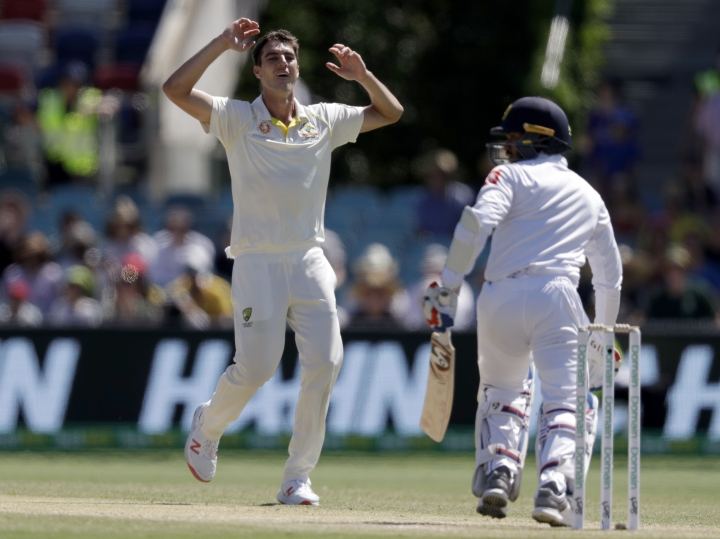 Australia's Pat Cummins, left, raises his arms after bowling to Sri Lanka's Dhananjaya de Silva, right, on day 3 of their cricket test match in Canberra, Sunday, Feb. 3, 2019. (AP Photo/Rick Rycroft)