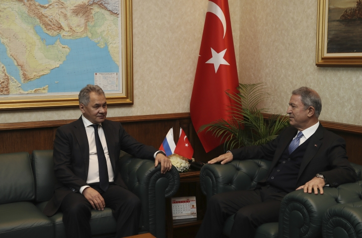 "Turkish Defence Minister Hulusi Akar, right, and Russia's Defence Minister Sergei Shoigu speak in Ankara, Turkey, Monday, Feb. 11, 2019. Shoigu said at the start of Monday's meeting with his Turkish counterpart Akar that the two countries' experts have done ""a lot of work to coordinate on issues related to the stabilization in Idlib and issues related to the east bank of the Euphrates River."" (Turkish Defence Ministry via AP, Pool)"