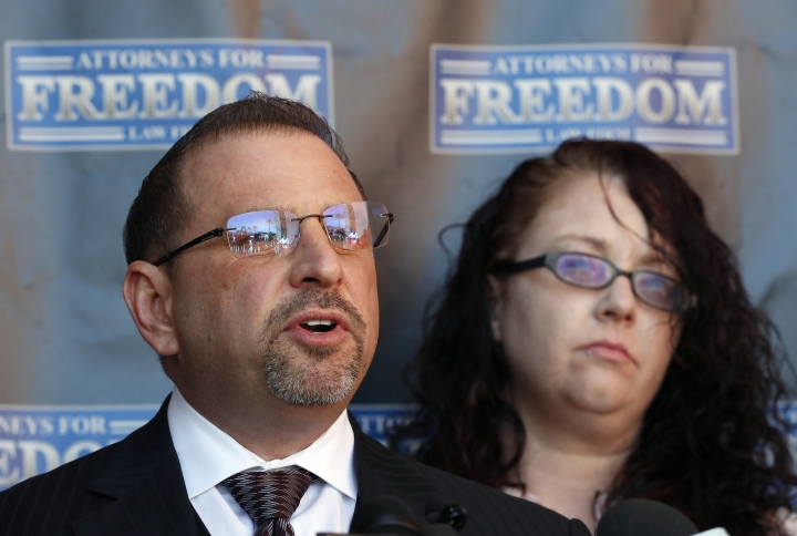 Attorney Marc J. Victor speaks to the media concerning his client, Johnny Wheatcroft, Monday, Feb. 11, 2019, in Chandler, Ariz. as Wheatcroft's wife, Anya Chapman, right, listens. Victor has filed a lawsuit on behalf of Wheatcroft claiming the Glendale, Ariz. police dept. used excessive force against Wheatcroft during his arrest in 2017. (AP Photo/Matt York)