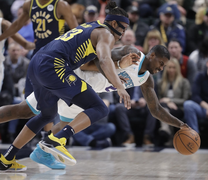 Indiana Pacers' Myles Turner, left, and Charlotte Hornets' Marvin Williams, right, battle for a loose ball during the first half of an NBA basketball game, Monday, Feb. 11, 2019, in Indianapolis. (AP Photo/Darron Cummings)