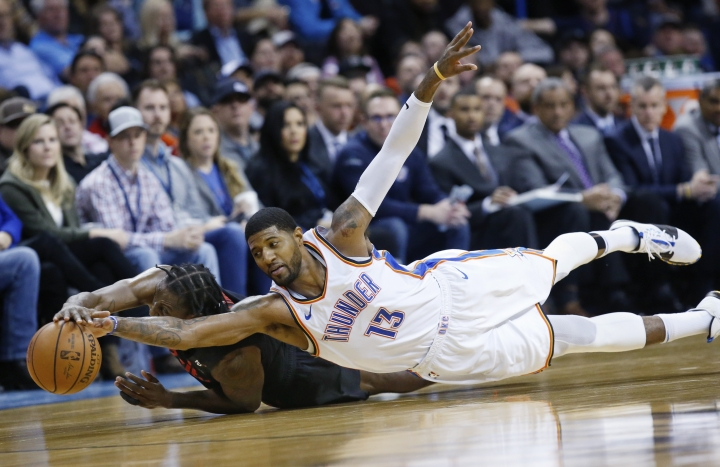 Oklahoma City Thunder forward Paul George (13) dives for the ball with Portland Trail Blazers forward Al-Farouq Aminu, left, in the second half of an NBA basketball game in Oklahoma City, Monday, Feb. 11, 2019. (AP Photo/Sue Ogrocki)