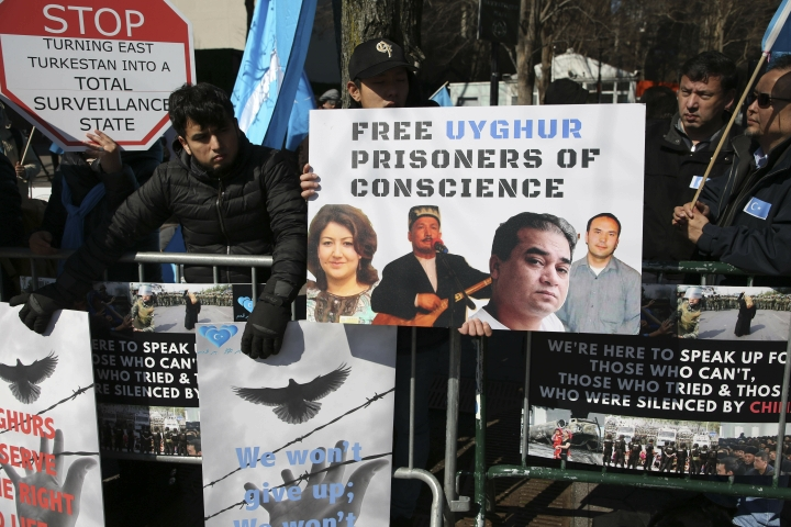 FILE - In this March 15, 2018, file photo, Uighurs and their supporters rally across the street from United Nations headquarters in New York. Members of the Uighur Muslim ethnic group are calling on China to post videos of their relatives who have disappeared into a vast system of internment camps. The campaign follows the release of a state media video showing famed Uighur musician Abdurehim Heyit, who many believed had died in custody. (AP Photo/Seth Wenig, File)