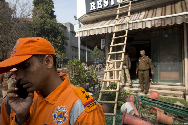 A rescuer from the National Disaster Response Force speaks on the mobile phone after an early morning fire killed more than a dozen people at the Arpit Palace Hotel in the Karol Bagh neighborhood of New Delhi, India, Tuesday, Feb.12, 2019. (AP Photo/Manish Swarup)