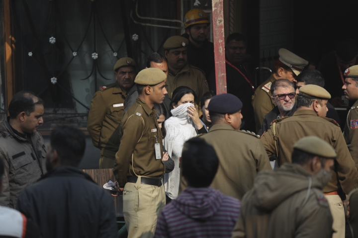Policemen and others stand at the spot after an early morning fire at the Arpit Palace Hotel killed more than a dozen people in the Karol Bagh neighborhood of New Delhi, India, Tuesday, Feb.12, 2019. (AP Photo/Manish Swarup)