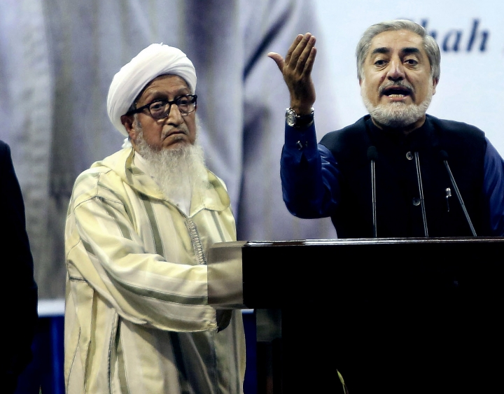 FILE- In this Sept. 9, 2014, file photo, former Afghan President Sibghatullah Mujadidi, left, accompanies Afghan presidential candidate Abdullah Abdullah, right, during a ceremony honoring a beloved anti-Taliban fighter who was assassinated 13 years ago, in Kabul, Afghanistan. Mujadidi, who served as Afghanistan's first president following the ouster of the invading Soviet army and the collapse in 1992 of Kabul's pro-Communist government, dies. He was 93. His former spokesman Sharif Yusufi says Mujadidi died overnight Tuesday, Feb. 12, 2019, in the Afghan capital.(AP Photo/Rahmat Gul, File)