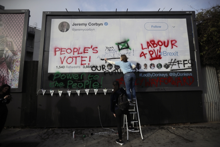 "Young members of Britain's opposition Labour party write on a billboard why they want Jeremy Corbyn the party leader to back a ""People's Vote"" second referendum on Britain's European Union membership, during a publicity stunt in Islington North, Corbyn's north London constituency, Tuesday, Feb. 12, 2019. The event was organized Tuesday by ""For our Future's Sake"" (FFS), a nationwide group of students and young people working to stop Brexit, with the billboard provided by ""Led By Donkeys"" a remain supporting group using online crowd funding to pay for billboard space to put up posters highlighting quotes on Brexit made by politicians and organizations. (AP Photo/Matt Dunham)"