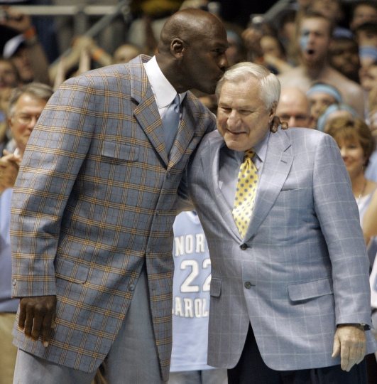 File-This Feb. 10, 2007, file photo shows former North Carolina player Michael Jordan, left, giving his former coach Dean Smith a kiss during halftime of a college basketball game between North Carolina and Wake Forest in Chapel Hill, N.C. It's well-known that Jordan uses failure to motivate him. The only thing seemingly that has eluded the 55-year-old Jordan is ultimate success as an executive and team owner. His Hornets have yet to win a playoff series since he took over as majority owner nine years ago and they remain marred in NBA mediocrity while struggling to compete in a small market. But Jordan wants to keep his team, and the city, relevant. It's one reason he aggressively pursued the All-Star game with such vigor. (AP Photo/Gerry Broome, File)