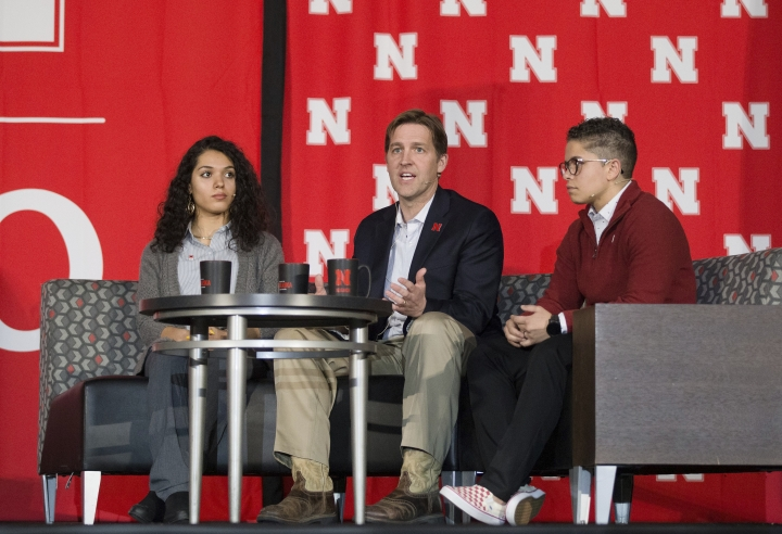 """In this Monday, Feb. 11, 2019 photo, U.S. Ben Sasse, R-Neb., answers a question posed to him during a panel discussion for the University of Nebraska's Charter Week Celebration while students Grace Chambers, left, and Kamryn Sannicks listen in Lincoln, Neb. Sasse said technology has undermined traditional community structures, and ideology or """"political tribes"""" are rushing to fill the void. He said political parties aren't adequate replacements for communities. (Maddie Washburn/Omaha World-Herald via AP)"""