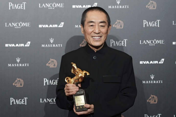 "FILE - In this Saturday, Nov. 17, 2018, file photo, Chinese director Zhang Yimou holds his award for Best Director at the 55th Golden Horse Awards in Taipei, Taiwan. The latest film from Zhang has been dropped from the Berlin International Film Festival for ""technical reasons."" A notice on the official account of the movie ""One Second"" on China's Weibo microblogging service apologized, but gave no details other than to say it was not possible to show the film at Berlin. (AP Photo/Billy Dai, File)"