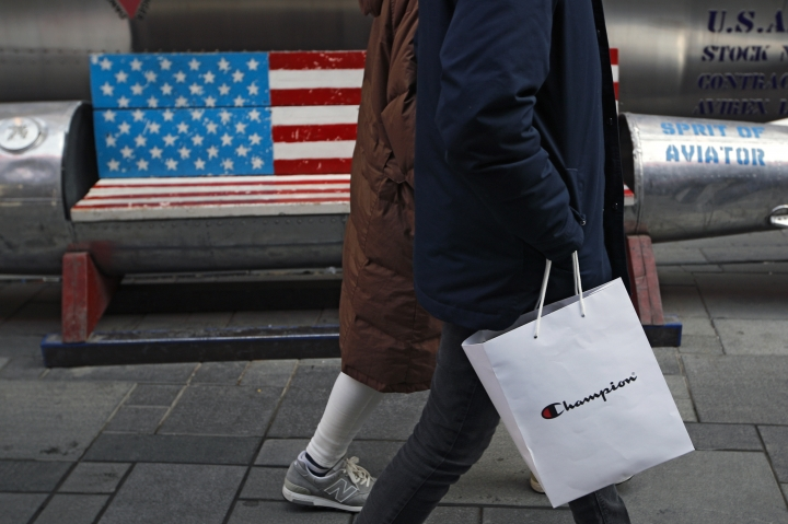 A couple carries a paper bag containing goods purchased from American brand Champion past a bench painted with the U.S. flag at the capital city's popular shopping mall in Beijing, Wednesday, Feb. 13, 2019. U.S. and Chinese negotiators are meeting this week for their final trade talks before President Donald Trump decides whether to escalate a dispute over technology with a March 2 tariff hike on $200 billion of imports from China. (AP Photo/Andy Wong)