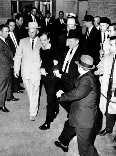 FILE- In this Nov. 24, 1963, file photo President John F. Kennedy assassin Lee Harvey Oswald, center in handcuffs, is shot by Jack Ruby, foreground, in the underground garage of the Dallas police headquarters. On Tuesday, Feb. 12, 2019, Chuck Green, a former Associated Press foreign correspondent and chief of bureau, died. Green reported the death of Oswald. (Jack Beers/The Dallas Morning News via AP, File)