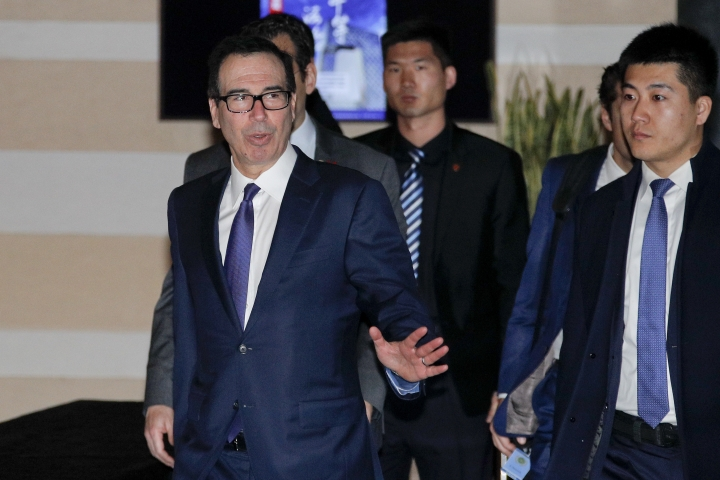 U.S. Treasury Secretary Steven Mnuchin, left, gestures to journalists as he leaves a hotel to attend a new round of high-level trade talks with Chinese officials in Beijing, Thursday, Feb. 14, 2019. (AP Photo/Andy Wong)