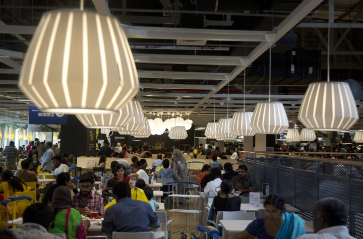 FILE- In this Aug. 9, 2018, file photo, customers sit at the restaurant inside Ikea's's first store in India as it opened in Hyderabad, India. In Hyderabad's bustling Nampally furniture market, customers explore a crowded labyrinth of shops, haggle over prices and work with carpenters to design made-to-order housewares. This is the competition Swedish giant Ikea faces in tackling the $40 billion Indian market for home furnishings, which is growing quickly along with the country's consumer class. (AP Photo/Mahesh Kumar A, file)