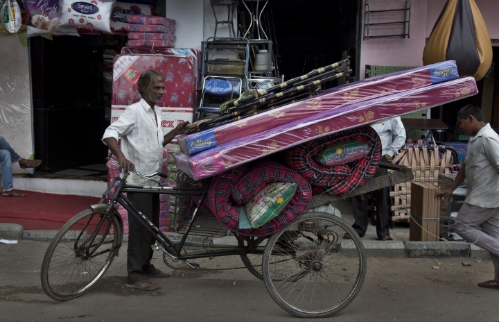 In this Dec. 17, 2018, photo, a cycle rickshaw puller prepares to transport mattresses from the Nampally furniture market in Hyderabad, India. Just 20 kilometers (12 miles) from Hyderabad's Ikea, Nampally remains a beehive of activity, demand for India's traditional custom-built furniture remains high. But Ikea already is adding to pressure on Indian furniture sellers' profits and could eventually take a bigger bite of the market. (AP Photo/Mahesh Kumar A.)