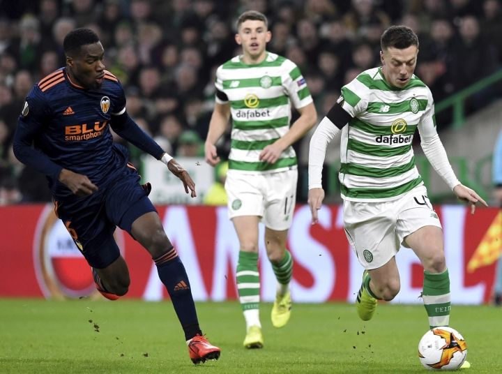 Valencia's Geoffrey Kondogbia left, view for the ball with Celtic's Callum McGregor during the Europa League round of 32, first leg soccer match between Celtic and Valencia, at Celtic Park, in Glasgow, Scotland, Thursday, Feb. 14, 2019. (Ian Rutherford/PA via AP)