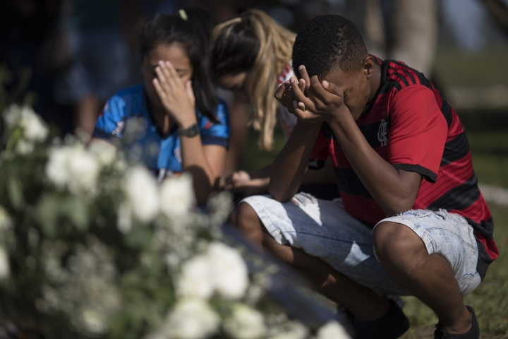 Friends grieve during the burial of the young soccer player Arthur Vinicius, one of the victims of a fire at a Brazilian soccer academy, in Volta Redonda, Brazil, Saturday, Feb. 9, 2019. A fire early Friday swept through the sleeping quarters of an academy for Brazil's popular professional soccer club Flamengo, killing several and injuring others, most likely teenage players, authorities said. (AP Photo/Leo Correa)
