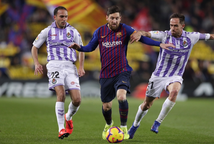 Barcelona forward Lionel Messi, center, challenges for the ball with Valladolid's Nacho Martinez, left, and Michel Herrero during the Spanish La Liga soccer match between FC Barcelona and Valladolid at the Camp Nou stadium in Barcelona, Spain, Saturday, Feb. 16, 2019. (AP Photo/Manu Fernandez)
