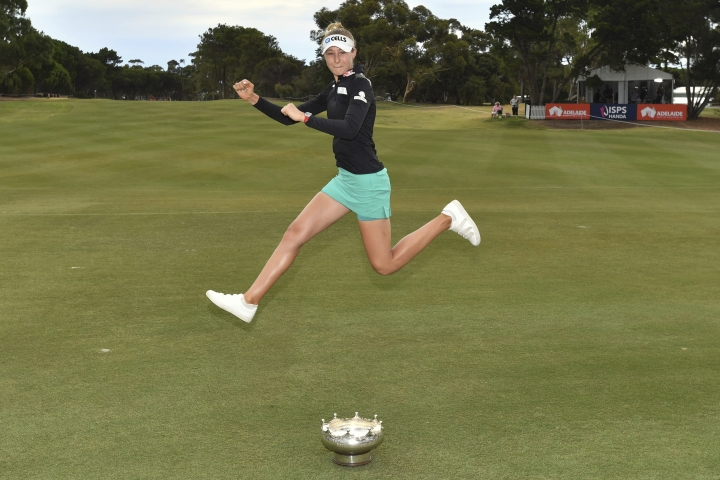 Nelly Korda of the United States jumps over her trophy as she celebrates her win in the Women's Australian Open golf tournament in Adelaide, Australia Sunday, Feb. 17, 2019. (AAP Image/David Mariuz)