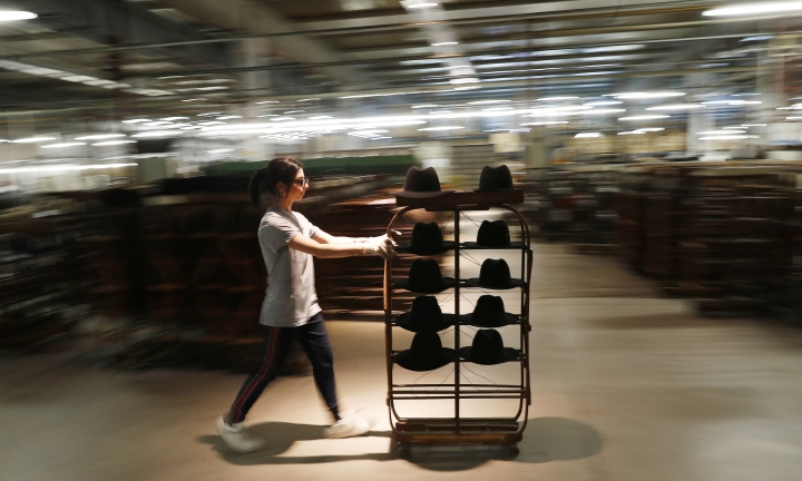 A woman worker pushes a cart with hats in Borsalino's hat factory, in Spinetta Marengo, near Alessandria, Italy, Thursday, Jan. 17, 2019. Borsalino's prized felt hats are handmade by 80 workers in its Piemonte factory, many who have worked there for decades, with original machinery that use hot water and steam to transform rabbit fur into highly prized felt, that is formed into clochards, dyed and molded by hand to create the latest styles. (AP Photo/Antonio Calanni)