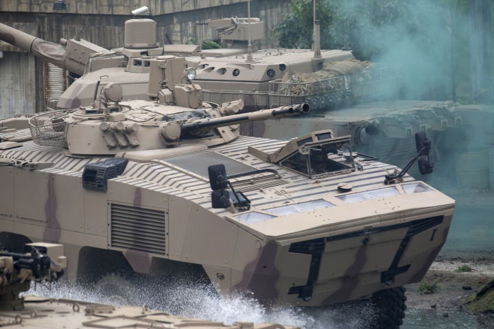 Soldiers in an armored personnel carrier roar through a military demonstration at the International Defense Exhibition and Conference in Abu Dhabi, United Arab Emirates, Sunday, Feb. 17, 2019. The biennial arms show in Abu Dhabi comes as the United Arab Emirates faces increasing criticism for its role in the yearlong war in Yemen. (AP Photo/Jon Gambrell)