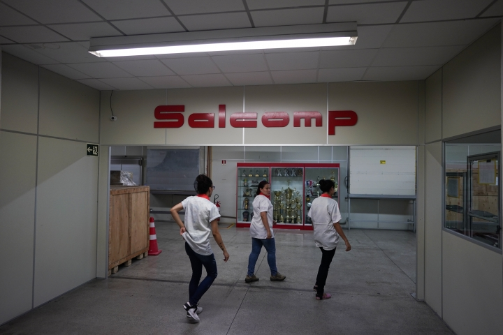 Workers enter the Salcomp factory, which makes chargers and adapters, where employee's sports trophies are displayed in Manaus, Brazil, Thursday, Feb. 14, 2019. They left the factory only 90 minutes before their soccer kickoff, excited for the chance to play a final in front of thousands of fans in Manaus' 2014 World Cup stadium, the Arena da Amazonia. (AP Photo/Victor R. Caivano)