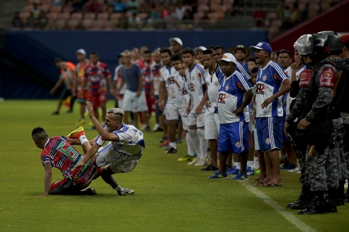 "Alvorada striker Neymar Junior, center, falls while fighting for the ball as players invade the pitch during the Peladao final amateur soccer tournament at Arena da Amazonia in Manaus, Brazil, Saturday, Feb. 16, 2019. Many players had eye-catching hairstyles, many trying to copy whatever style Neymar had throughout his career and others whose hair carries inscriptions like ""I love Jesus."" (AP Photo/Victor R. Caivano)"