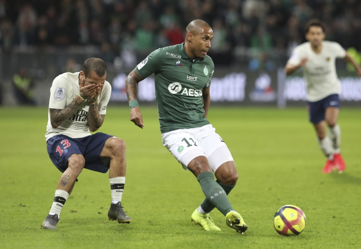 Saint-Etienne's Gabriel Silva, right, challenges for the ball as PSG defender Dani Alves covers his face after he was hurt during the French League One soccer match between Saint-Etienne and Paris Saint-Germain, at the Geoffroy Guichard stadium, in Saint-Etienne, central France, Sunday, Feb. 17, 2019. (AP Photo/Laurent Cipriani)