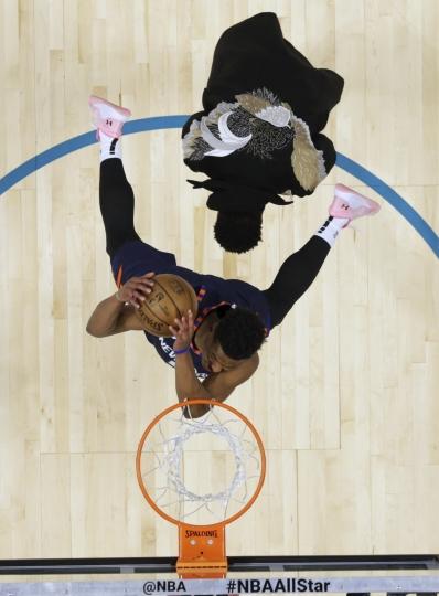 New York Knicks Dennis Smith Jr. dunks over Miami Heat player Dwyane Wade during the NBA All-Star Slam Dunk contest, Saturday, Feb. 16, 2019, in Charlotte, N.C. (AP Photo/Chuck Burton, Pool)