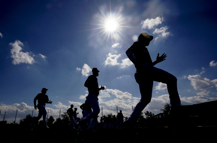 Milwaukee Brewers players run a drill during a spring training baseball workout Sunday, Feb. 17, 2019, in Phoenix. (AP Photo/Morry Gash)