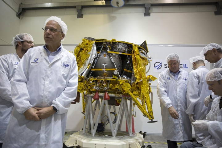 "File - In this Monday, Dec. 17, 2018 file photo, technicians stand next to the SpaceIL lunar module, an unmanned spacecraft, is on display in a special ""clean room"" where the space craft is being developed, during a press tour of their facility near Tel Aviv, Israel. SpaceIL and state-owned Israel Aerospace Industries told a news conference that the landing craft will take off from Florida, to its weekslong voyage to the moon this week. (AP Photo/Ariel Schalit, File)"