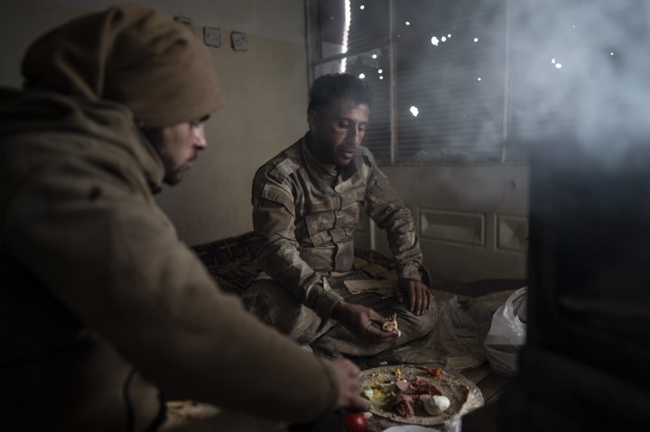 U.S.-backed Syrian Democratic Forces (SDF) fighters eat in a building as the fight against Islamic State militants continues in the village of Baghouz, Syria, Sunday, Feb. 17, 2019. Islamic State militants are preventing more than 1,000 civilians from leaving a tiny area still held by the extremist group in a village in eastern Syria, a spokesman for the U.S.-backed Syrian militia fighting the group said Sunday. (AP Photo/Felipe Dana)
