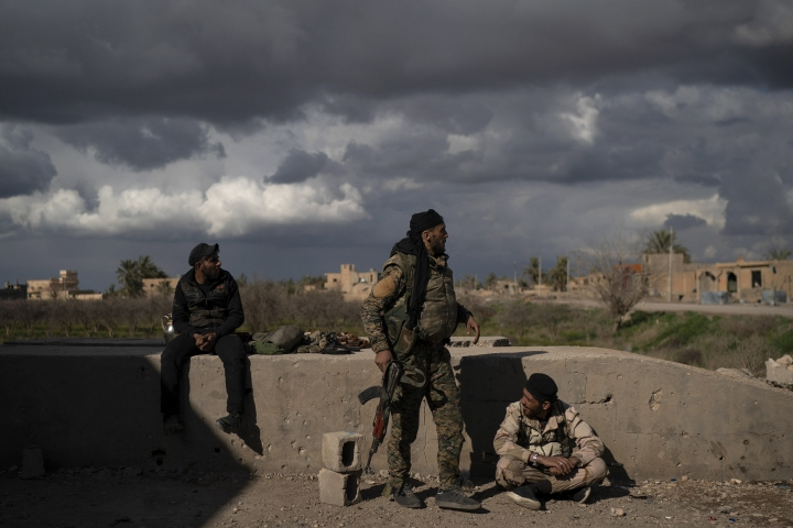 U.S.-backed Syrian Democratic Forces (SDF) fighters stand in an area recently taken by SDF as fight against Islamic State militants continue in the village of Baghouz, Syria, Sunday, Feb. 17, 2019. Islamic State militants are preventing more than 1,000 civilians from leaving a tiny area still held by the extremist group in a village in eastern Syria, a spokesman for the U.S.-backed Syrian militia fighting the group said Sunday. (AP Photo/Felipe Dana)