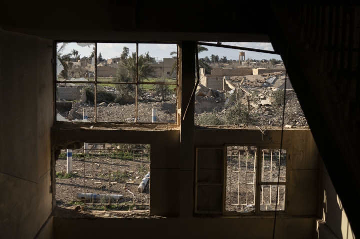 Destroyed homes are framed by damaged windows in a building taken by U.S.-backed Syrian Democratic Forces (SDF) near the last land still held by Islamic State militants in Baghouz, Syria, Monday, Feb. 18, 2019. Hundreds of Islamic State militants are surrounded in a tiny area in eastern Syria are refusing to surrender and are trying to negotiate an exit, Syrian activists and a person close to the negotiations said Monday. (AP Photo/Felipe Dana)
