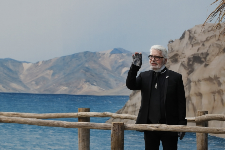 FILE - In this Tuesday, Oct.2, 2018 file photo, Karl Lagerfeld waves after the presentation of Chanel Spring/Summer 2019 ready-to-wear fashion collection in Paris. Chanel's iconic couturier, Karl Lagerfeld, whose accomplished designs as well as trademark white ponytail, high starched collars and dark enigmatic glasses dominated high fashion for the last 50 years, has died. He was around 85 years old. (AP Photo/Christophe Ena, File )