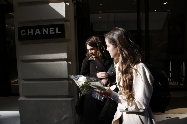 Well-wishers arrive to lay flowers in tribute to fashion designer Karl Lagerfeld at Chanel's headquarters in Paris, France, Tuesday, Feb. 19, 2019. Chanel's iconic couturier, Karl Lagerfeld, whose accomplished designs as well as trademark white ponytail, high starched collars and dark enigmatic glasses dominated high fashion for the past 50 years, has died. He was around 85 years old. (AP Photo/Michel Euler)