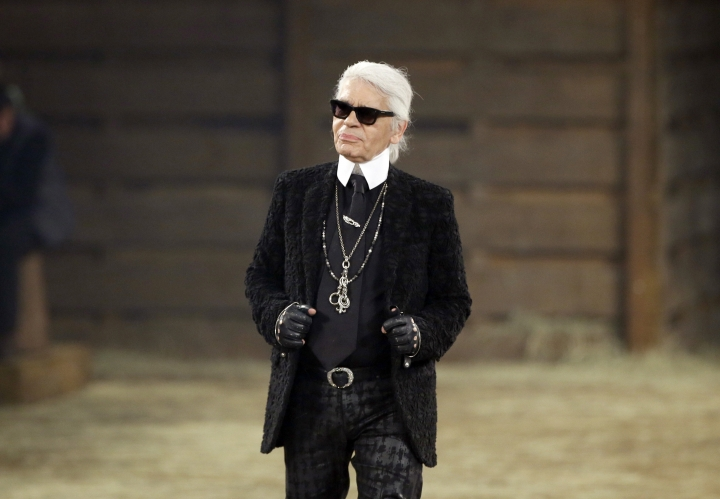 FILE - In this Tuesday, Dec. 10, 2013 file photo, Chanel designer Karl Lagerfeld takes a bow at the end of his Metiers d'Art fashion show, Tuesday, Dec. 10, 2013, in Dallas. Chanel's iconic couturier, Karl Lagerfeld, whose accomplished designs as well as trademark white ponytail, high starched collars and dark enigmatic glasses dominated high fashion for the last 50 years, has died. He was around 85 years old. (AP Photo/Tony Gutierrez, File)