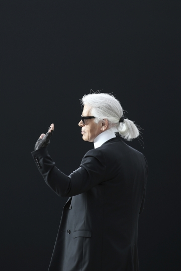 FILE - In this Tuesday, March 5, 2013 filer, Karl Lagerfeld waves after presenting the Chanel's Fall/Winter 2013-2014 ready to wear collection, in Paris. Chanel's iconic couturier, Karl Lagerfeld, whose accomplished designs as well as trademark white ponytail, high starched collars and dark enigmatic glasses dominated high fashion for the last 50 years, has died. He was around 85 years old. (AP Photo/Thibault Camus)