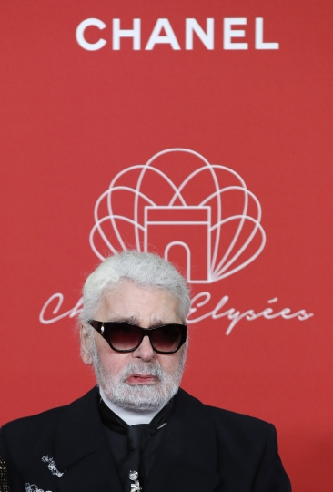 FILE - In this hursday, Nov. 22, 2018 file photo, Karl Lagerfeld poses during the Champs Elysee Avenue illumination ceremony for the Christmas season, in Paris. Chanel's iconic couturier, Karl Lagerfeld, whose accomplished designs as well as trademark white ponytail, high starched collars and dark enigmatic glasses dominated high fashion for the last 50 years, has died. He was around 85 years old. (AP Photo/Christophe Ena, File )