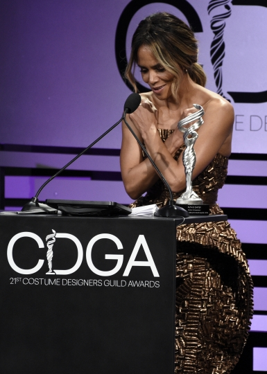 """Halle Berry gives the """"Wakanda Forever"""" gesture from the film """"Black Panther"""" as she presents the career achievement award to Ruth E. Carter at the 21st annual Costume Designers Guild Awards at The Beverly Hilton Hotel on Tuesday, Feb. 19, 2019, in Beverly Hills, Calif. (Photo by Chris Pizzello/Invision/AP)"""