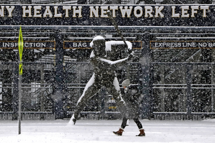 A pedestrian strolls past a statue of Pittsburgh Pirates Hall of Fame Willie Stargell outside the left field gate of PNC Park as snow falls during the morning rush-hour, Wednesday, Feb. 20, 2019, in Pittsburgh. (AP Photo/Gene J. Puskar)