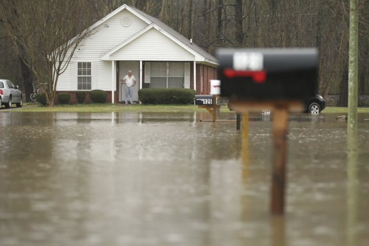 A homeowner can only watch from his front door as water levels rise near his house and flood the streets along Evergreen Drive in Saltillo, Mississippi Wednesday, February 20, 2019. Floodwaters covered roads on Wednesday in parts of eastern Mississippi and northern Alabama. (Thomas Wells/Northeast Mississippi Daily Journal, via AP)