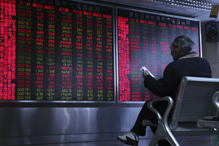 A Chinese man monitors stock prices at a brokerage in Beijing, China, Thursday, Feb. 21, 2019. Asian stock markets were little-changed Thursday following a listless day on Wall Street ahead of U.S.-Chinese negotiations aimed at ending a tariff battle. (AP Photo/Ng Han Guan)