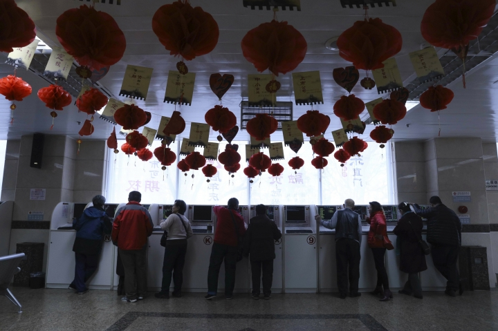 Investors monitor stock prices at a brokerage in Beijing, China, Thursday, Feb. 21, 2019. Asian stock markets were little-changed Thursday following a listless day on Wall Street ahead of U.S.-Chinese negotiations aimed at ending a tariff battle. (AP Photo/Ng Han Guan)