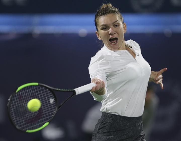 Romania's Simona Halep returns the ball to Switzerland's Belinda Bencic during their quarterfinal match of the Dubai Duty Free Tennis Championship in Dubai, United Arab Emirates, Thursday, Feb. 21, 2019. (AP Photo/Kamran Jebreili)
